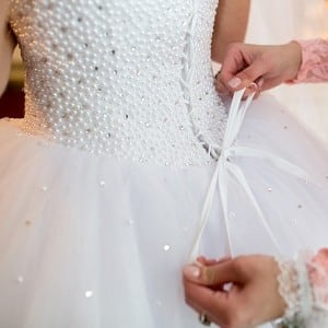 Bride in white lace dress getting assistance with tying lace ribbon on her dress