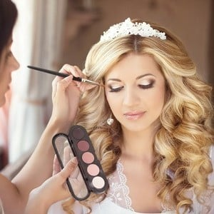 Bride with long blond hair and white headpiece having make up applied for wedding day