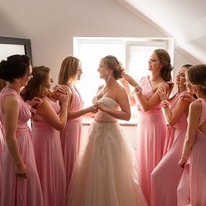 6 bridesmaid women dressed in pink helping bride get dressed