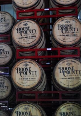 Eleven wooden barrels containing bourbon stacked on red shelves with the name Boone County printed on them