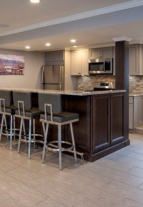 Kitchen with brown bar and three stools plus silver fridge, stove and microwave