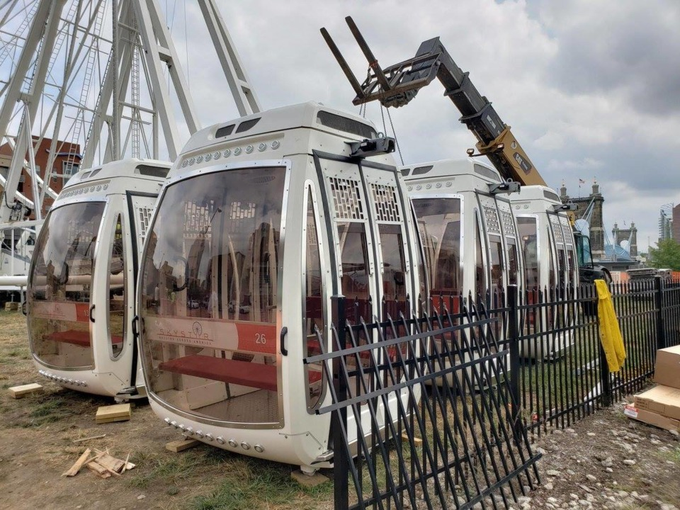 Gondola cars that are white and have glass on four sides sitting next to black fence