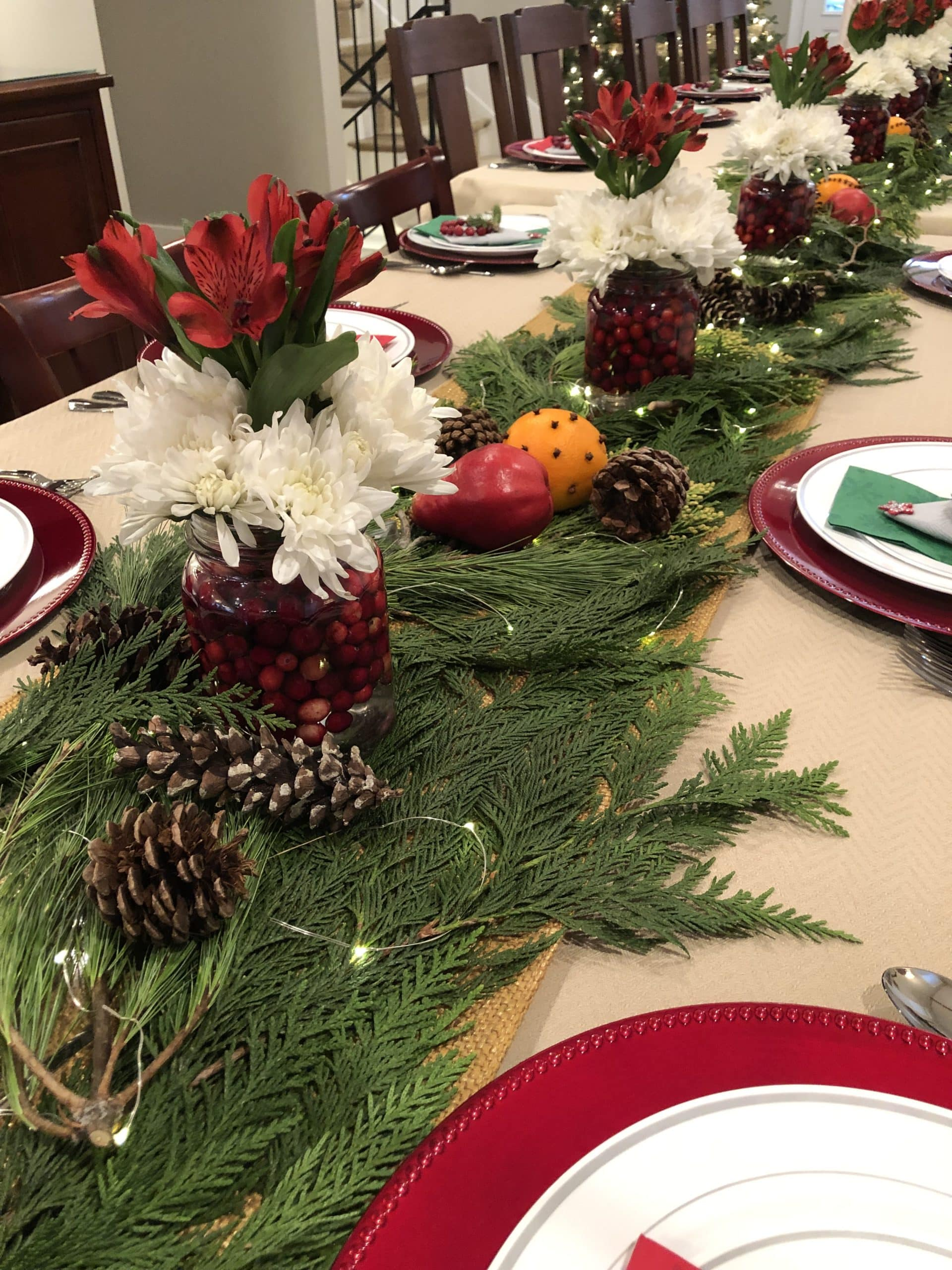 Table set with red and white plates with holiday greenery and flowers in the center