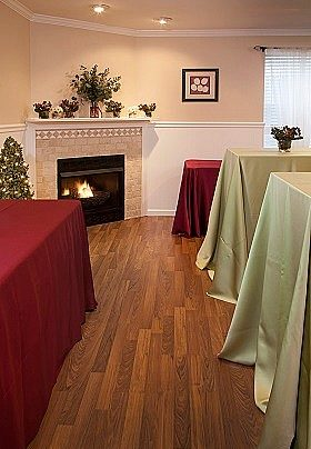Room with brick fireplace and tables covered in red and green linens