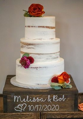 White 3 layer wedding cake with orange and burgundy flowers