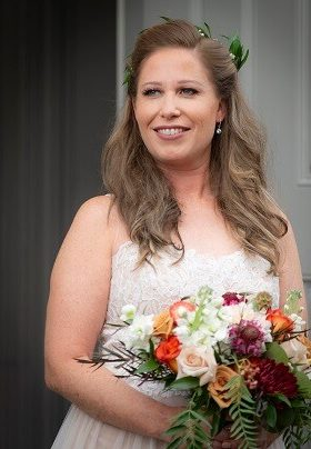 Bride holding floral arrangement with rust and burgundy flowers