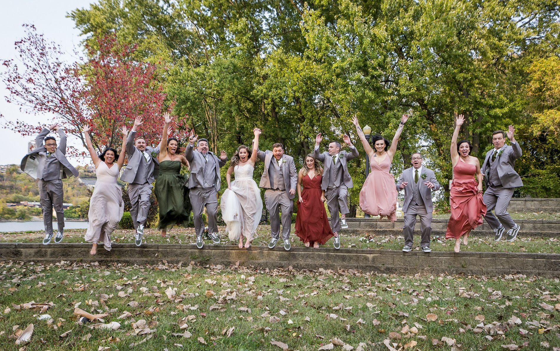 Group of ten men and women from a wedding jumping off a ledge