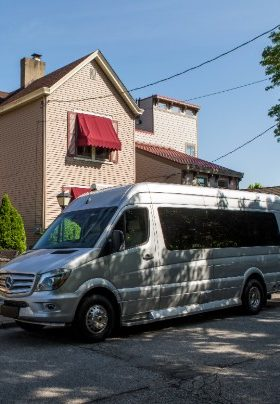 Large silver van with blackened windows in front of two-story tan house