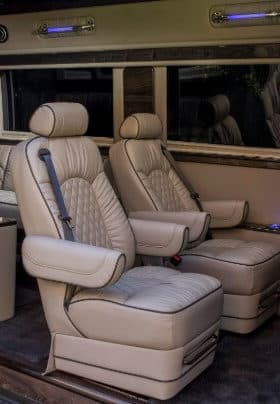 Two gray captains chairs with arm and head rest inside of a luxury van with blue horizontal lighting