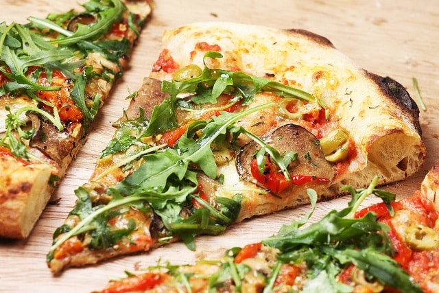 Three slices of pizza with red tomatoes and green arugula