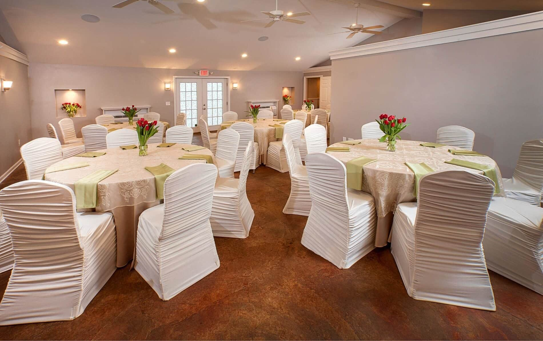 Large room with 6 round tables covered in beige lace tablecloths and white covered chairs