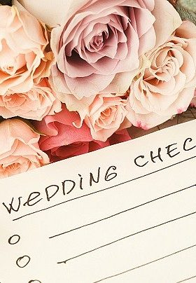 Pale peach and ivory roses with a paper labeled wedding checklist