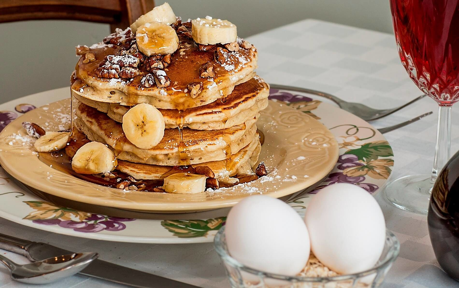 Four pancakes topped with bananas, pecans and syrup