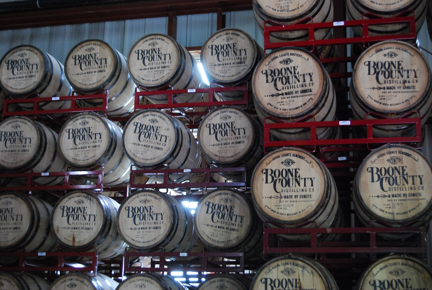 "24 wood barrells stamped with ""Boone County Distilling"" sitting on red racks"