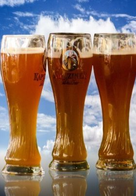Three tall glasses of amber colored beer in front of a bright blue sky with white clouds