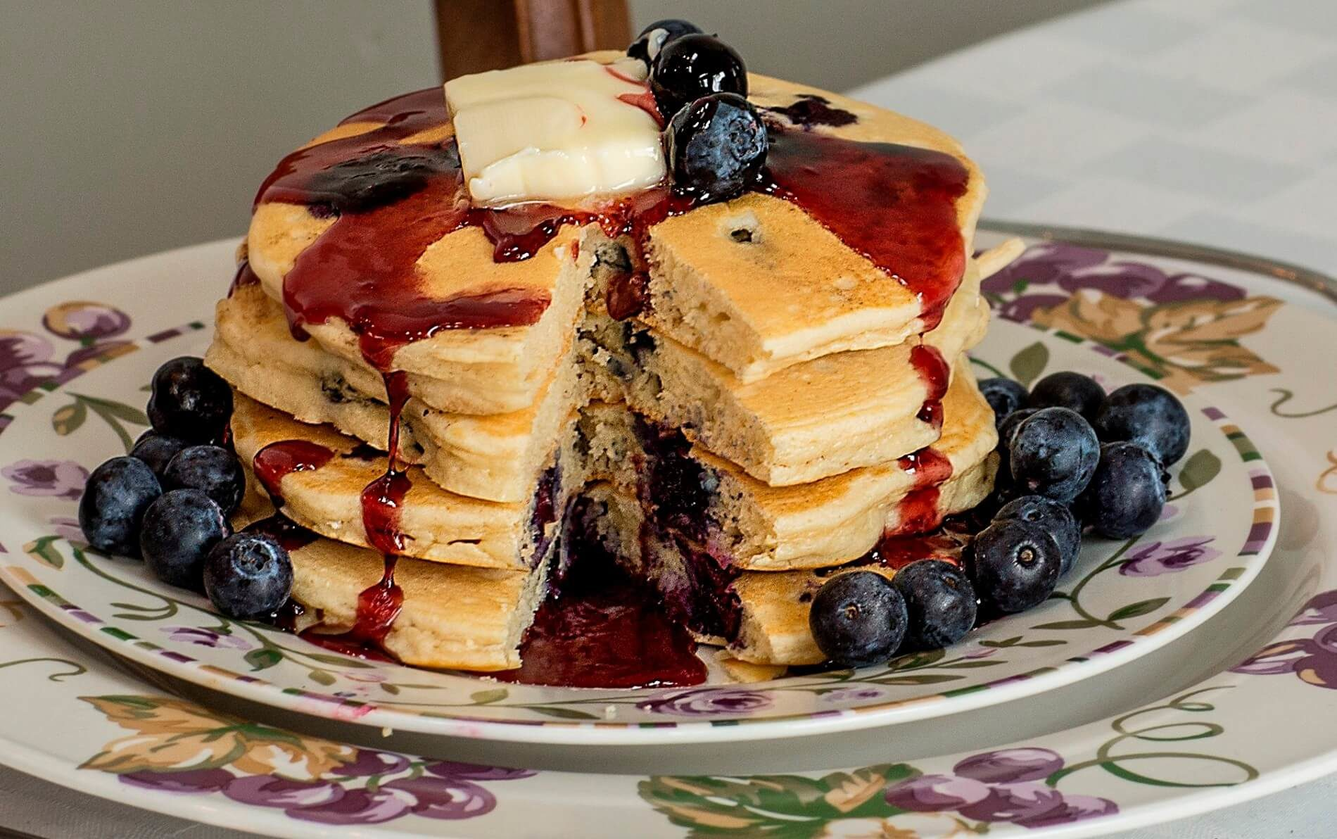 Purple flowered plates with stack of blueberry pancakes