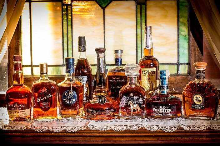Eleven bottles of bourbon sitting on a dresser with white lace