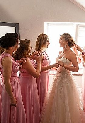 Bride in white dress surrounded by three bridesmaids in pink dresses