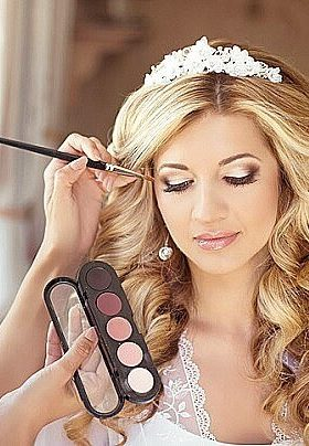 Bride with blonde hair and white heading getting assistance with her make up preparation