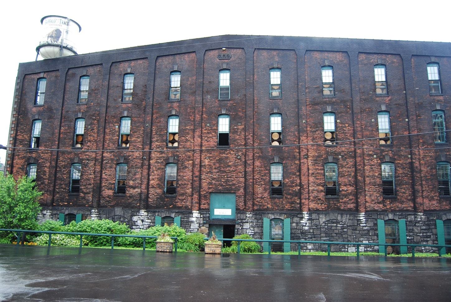 Three story red brick building with 31 tall windows trimmed in aqua displaying wooden barrels through the window