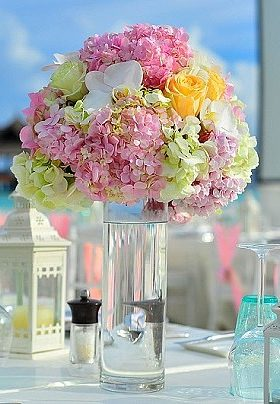 Table set with clear vase with pale pink and yellow roses and white lanterns as a centerpiece