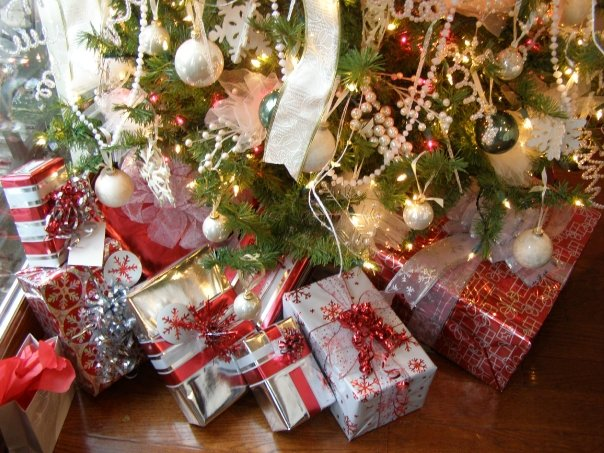 Green Pine tree decorated with red, white and silver ornaments and red and silver wrapped packages under the tree