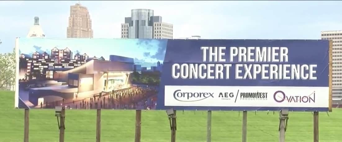 Blue and white sign with a picture of tan building and wording saying premier concert experience