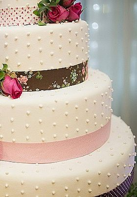 Three layer white wedding cake with pink flowers and brown and pink ribbon trim