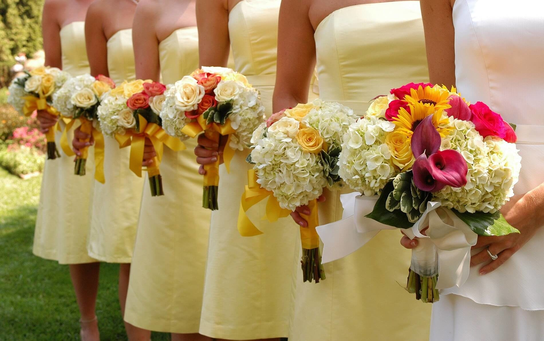 Bride in white dress with 5 bridesmaids in yellow dresses all with orange and yellow rose bouquets