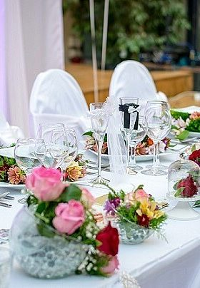Table with white table cloths and red and pink flowers