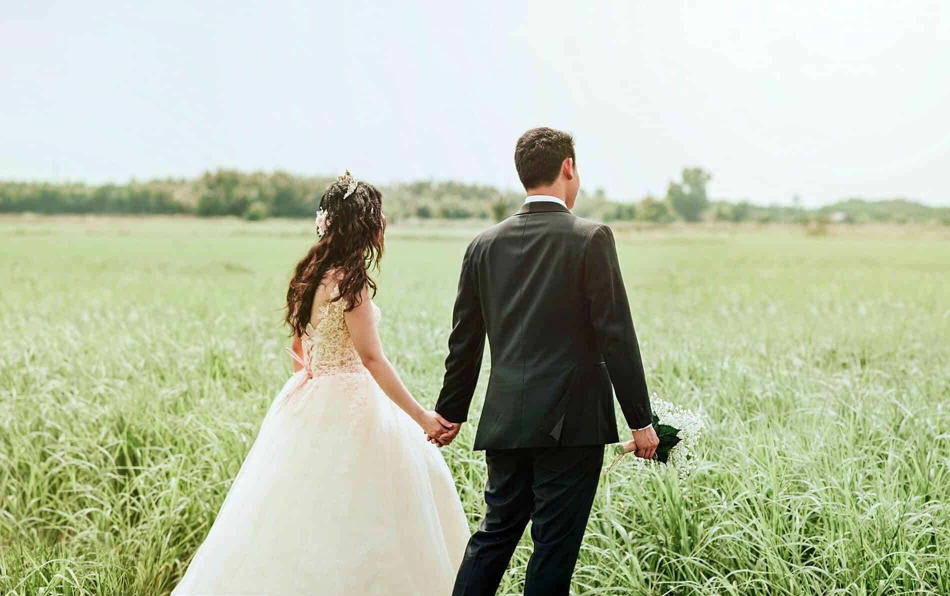 Bride in white dress holding hands with groom in black suite walking in open green field