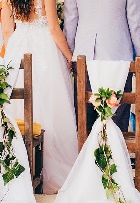 Bride and Groom standing in front of chairs decorated with white ribbon and pink flowers
