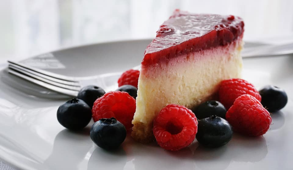Triangular piece of cheesecake with raspberry topping with blueberries and raspberries