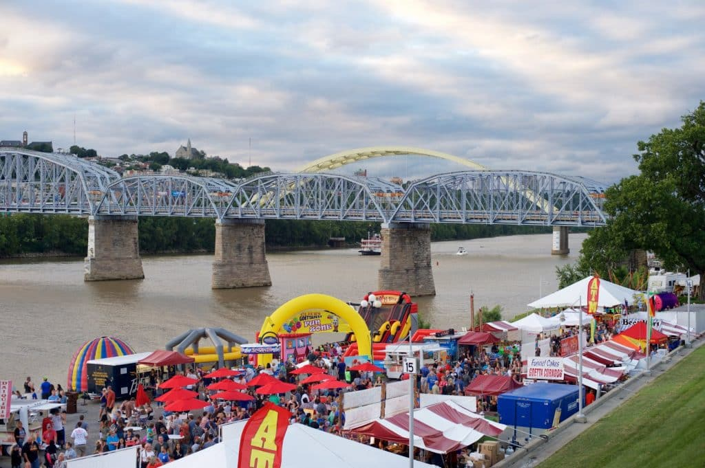 Purple bridge spanning a river with sidewalks set up with red and white tents and people mingling