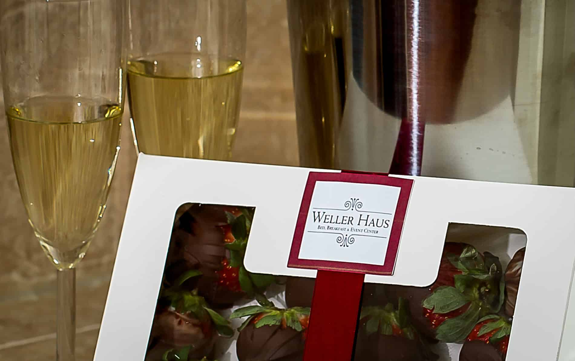 Two glasses of champagne with a white box tied with a red ribbon containing chocolate covered strawberries.