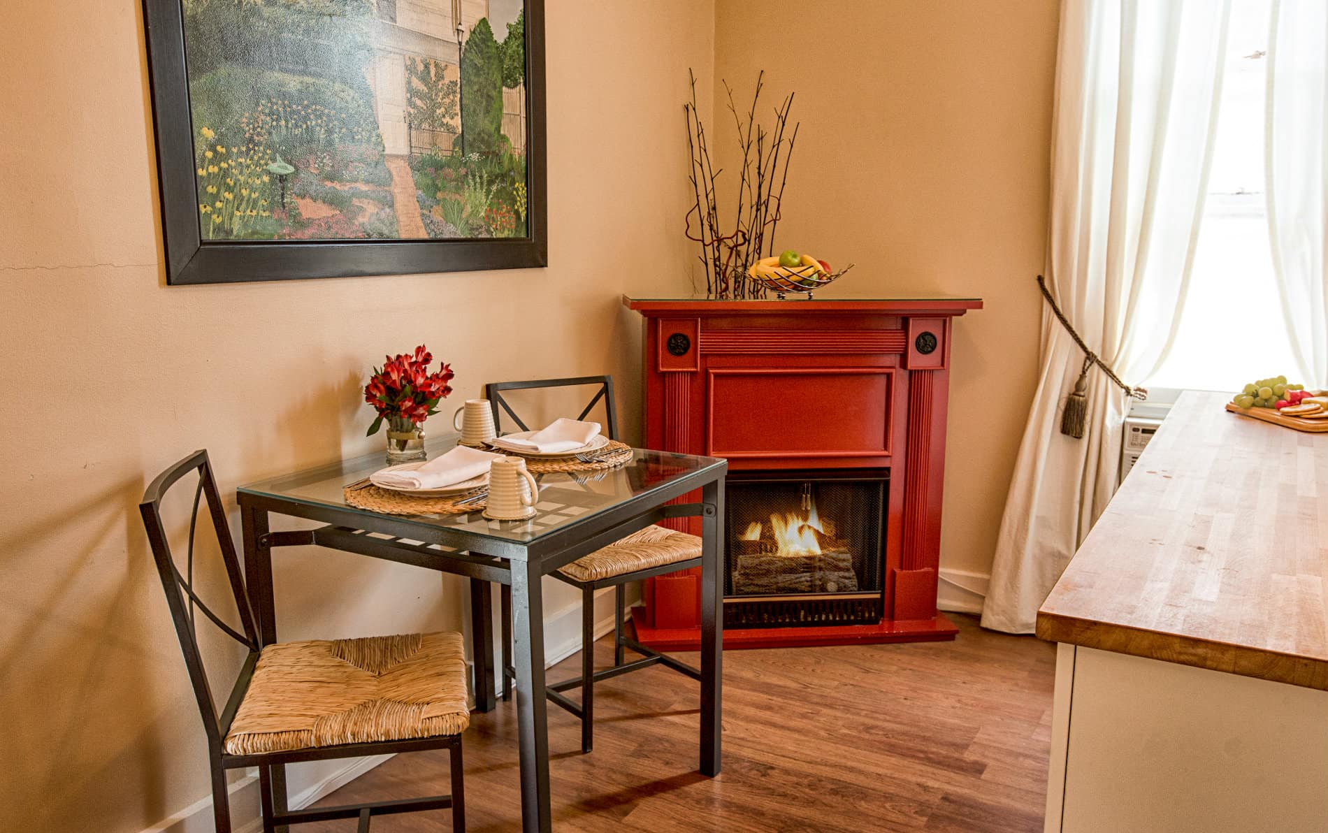 Sitting room with a red fireplace with burning fire, black iron table for two and picture of an outside garden