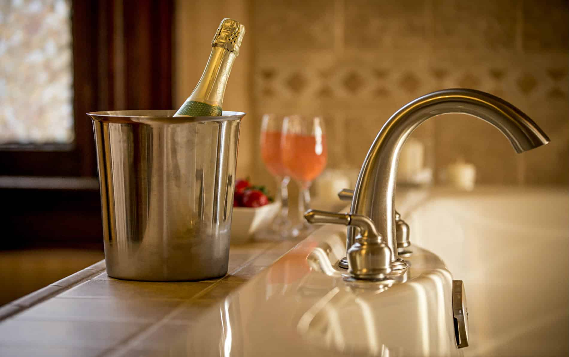 Large tub for two with a silver curved bathtub faucet. Silver bucket with champagne bottle , two glasses of pink champagne.