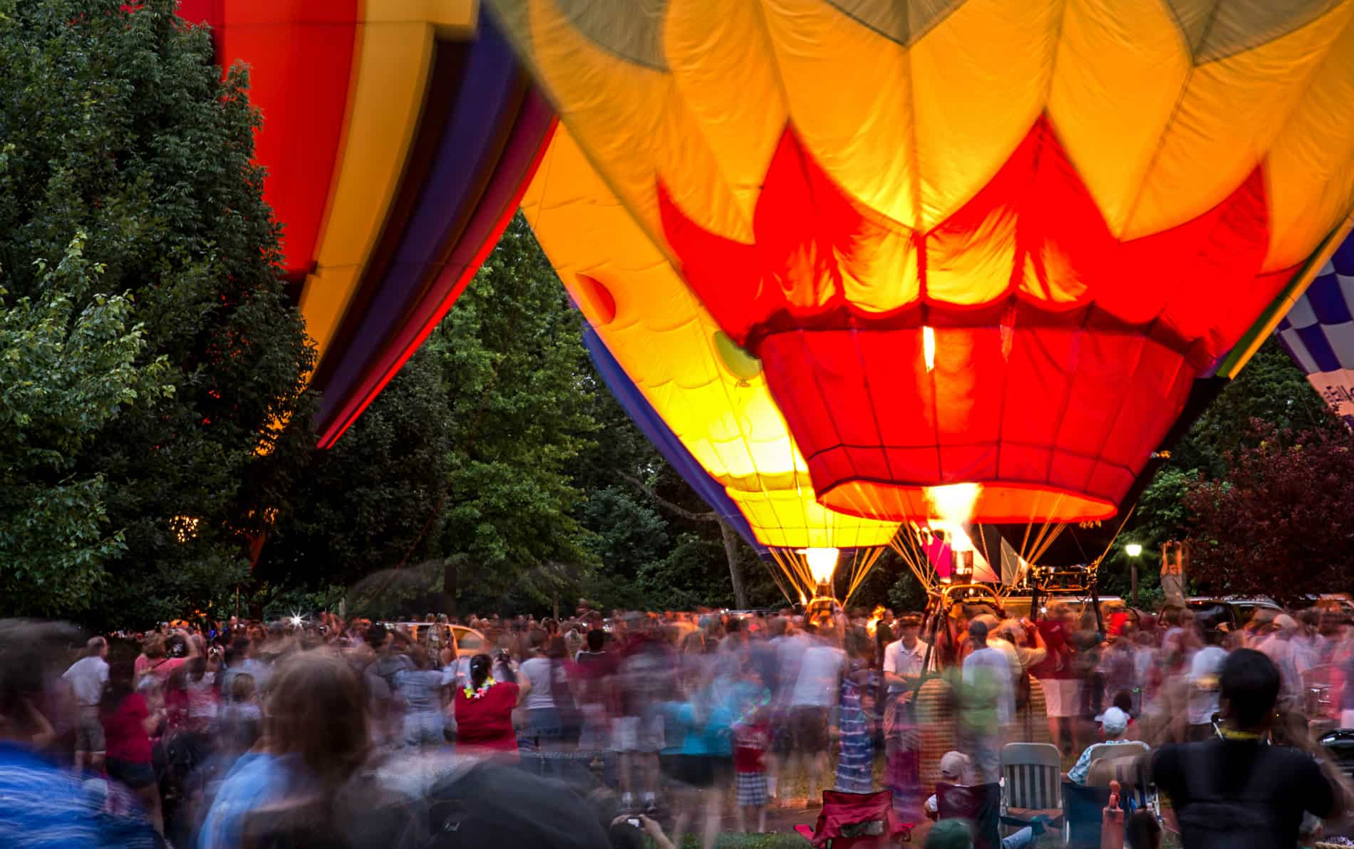 Red, yellow, green and blue hot air balloons surrounded by green trees and a crowd of people