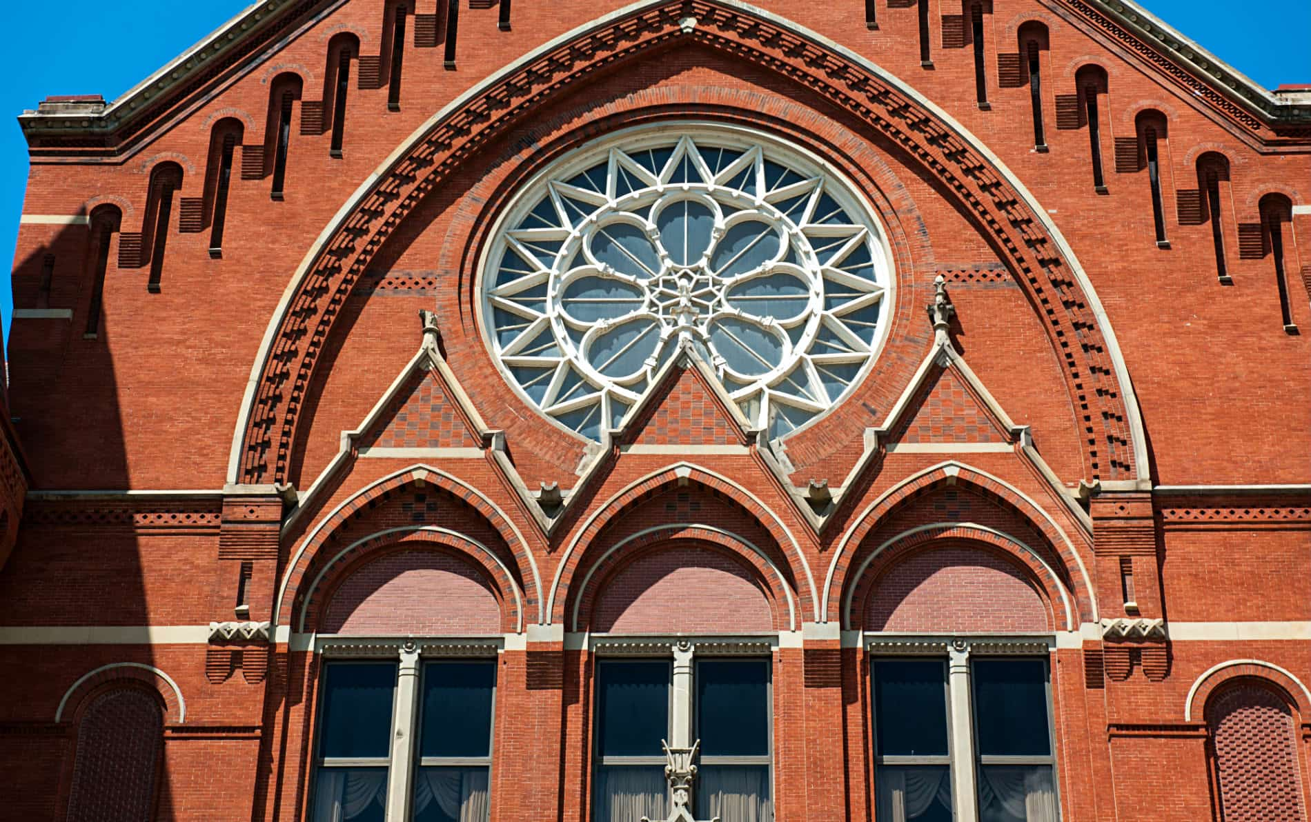 Historic red brick building with three arched windows