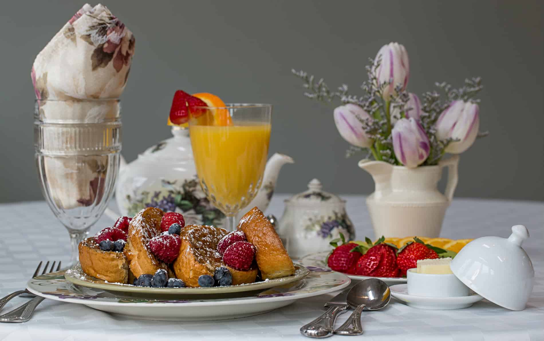 Sliced french toast with blueberries and raspberries, glass of orange juice, plate of sliced strawberries, small vase of purple tulips