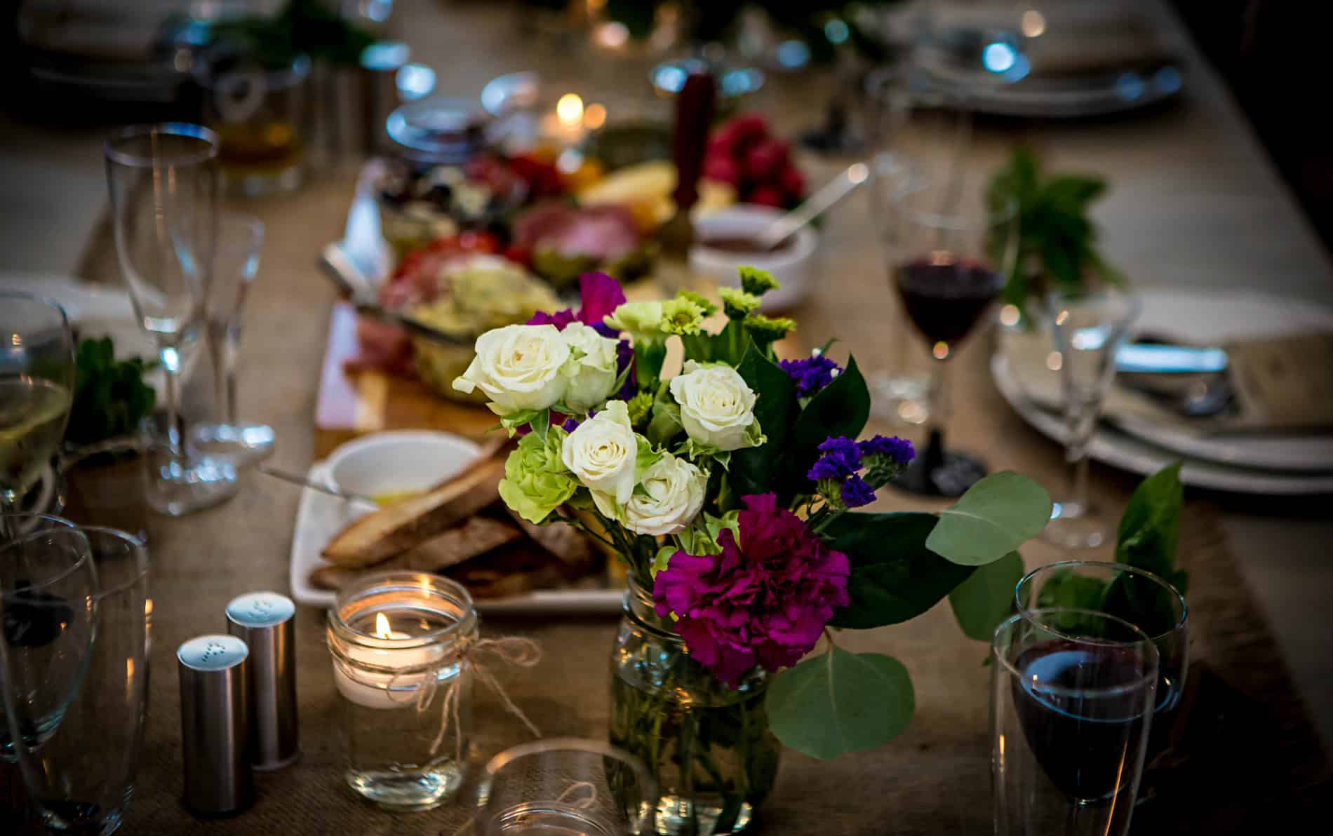 Dinner table set with red wine filled glasses, white plates, tan tablecloth, candles and white and purple flower arrangement.