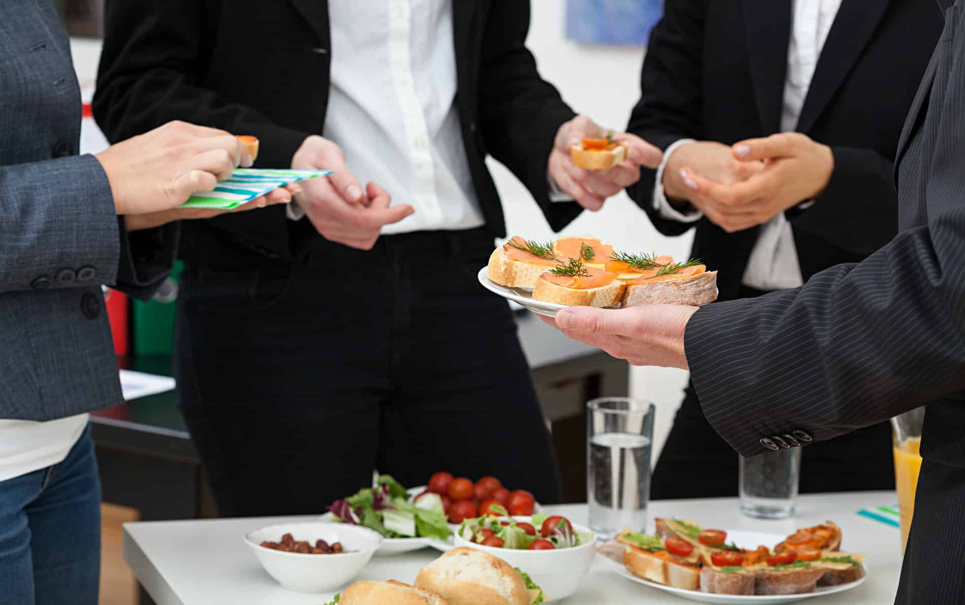 Four business people wearing dark suits with white shirts enjoying a green salad with red tomatoes, sliced bread and a clear beverage.