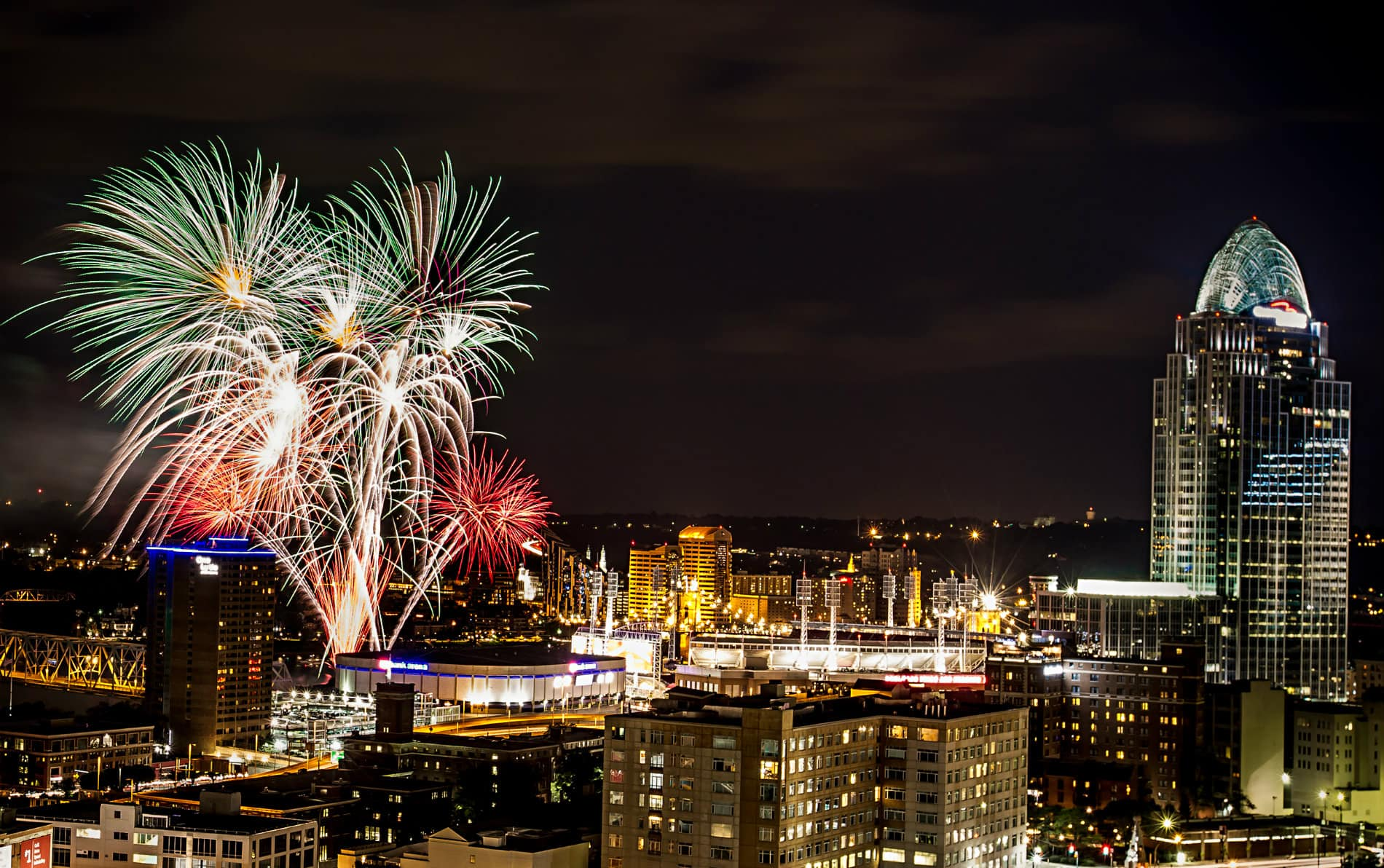 Lighted buildings with lights of blue, red, gold against a black night sky with red, green and white fireworks.