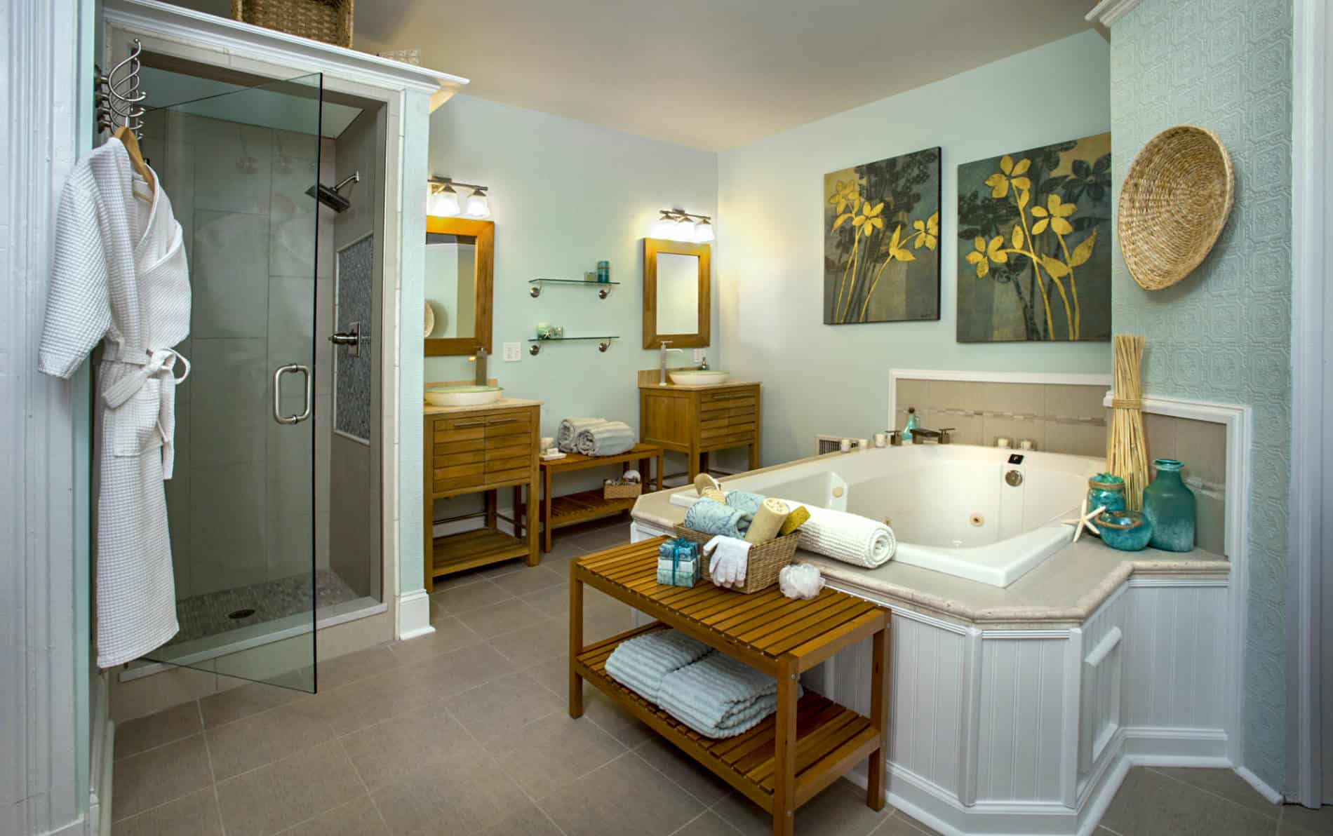 Room with large white tub, two wooden sink stands with green glass washbowls, pale green walls, and two wooden benches