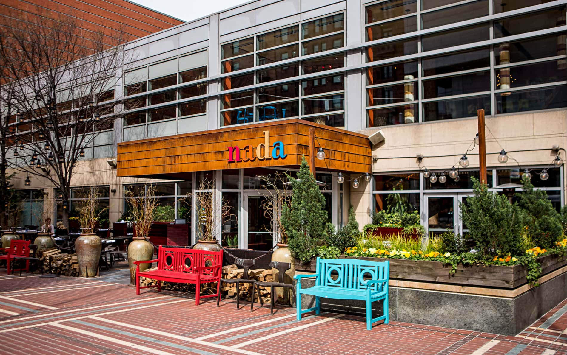 Long horizontal two-story restaurant building with 25 windows, aqua and red benches, planters with trees and yellow pansies