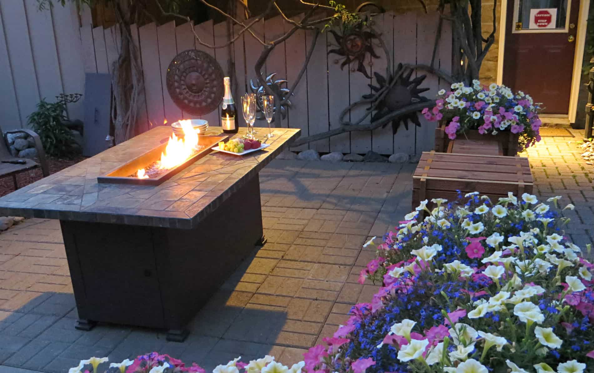 Rectangular table with fire in the middle, two glasses, champagne bottle and cheese tray with purple, pink and white flowers.