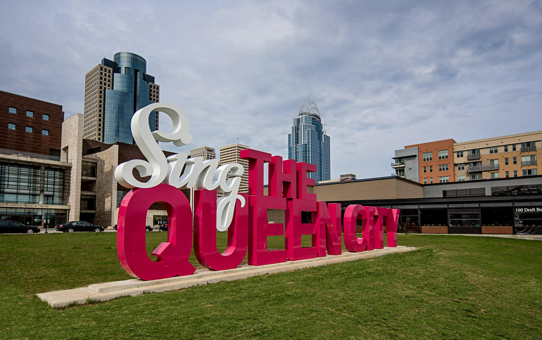 Large display sign in red and white letters spelling Sing the Queen City