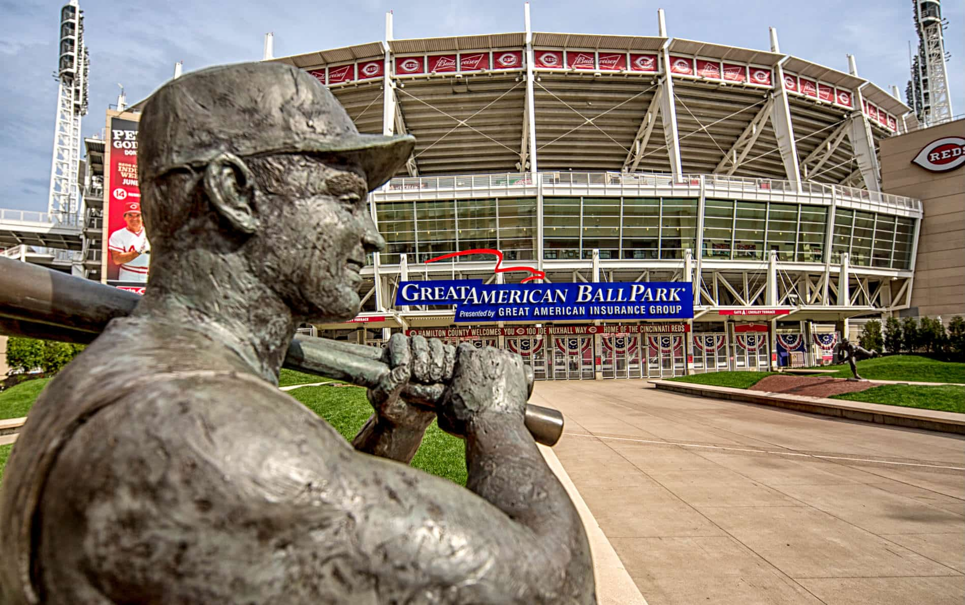 Large gray sculpture of baseball player in front of Great American Ballpark baseball stadium