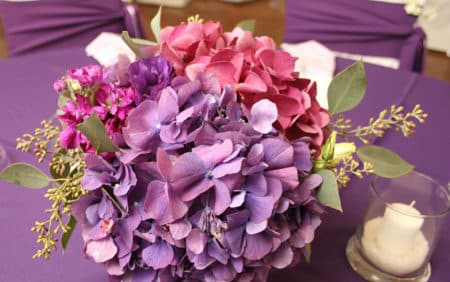 Arrangement of purple and pink hydrangeas on a purple table and white covered chairs with purple sash