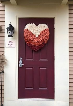 Red door with heart shaped floral of coral, rust and burgundy roses